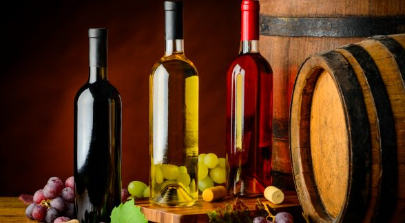 rose, white and red wine bottles on wooden table and with barrels.